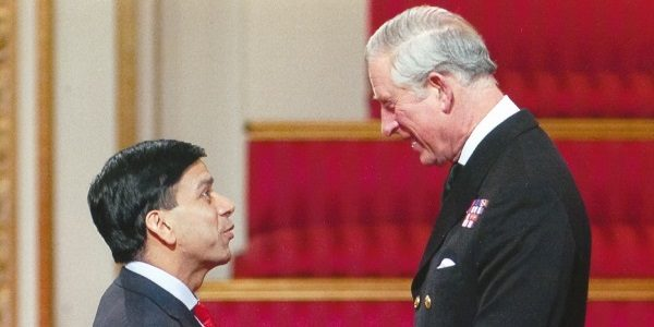 Prem receiving an OBE from The Prince of Wales for his services to the economy and promoting charitable giving